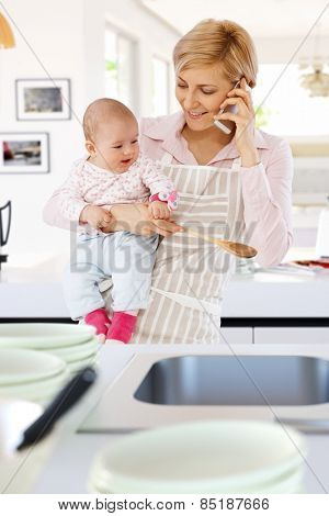Casual caucasian housewife in kitchen with baby, phone, spoon in hand. Standing, smiling, talking on phone.