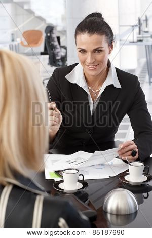 Mid adult caucasian brunette businesswoman signing contract over coffee at office table. Smiling, suit, pen in hand, focus in background.