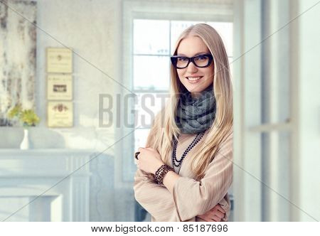 Young blonde caucasian casual artist woman with glasses at vintage home. Standing, smiling, looking at camera, arms crossed. Elegant.