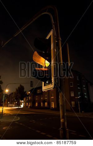 Flashing yellow on a traffic light at night.