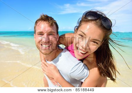 Young couple having fun laughing on beach holidays. Beautiful Asian mixed race woman piggybacking on Caucasian male excited at camera portrait. Multicultural, multiethnic, multiracial people.