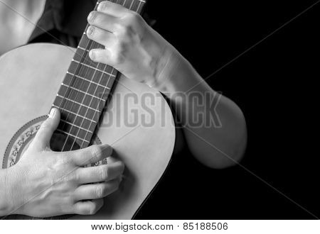 Acoustic guitar detail - Musician hands playing a classic guitar isolated on black