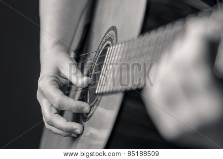 Acoustic guitar detail on black and white - Musician hands playing a classic guitar isolated on a black background