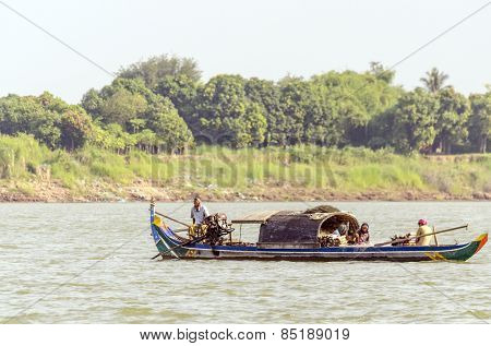 PHNOM PENH, CAMBODIA, JANUARY 2, 2013: Local fishermen travel by boat on Mekong river