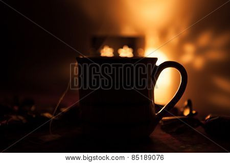 Steaming hot cup of tea next to a candle.