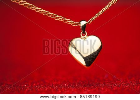 gold heart pendant on red background