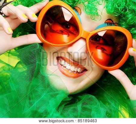 Happy young  woman with green hair and carnaval glasses