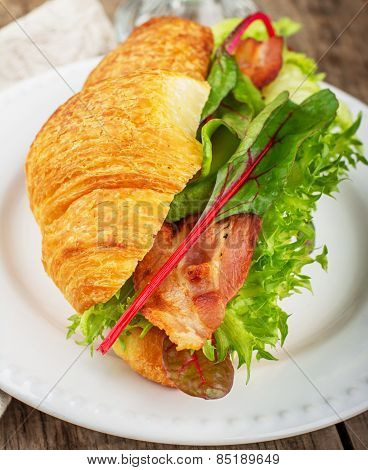Fresh croissant for breakfast stuffed with bacon, lettuce, chard, and avocado on a light background