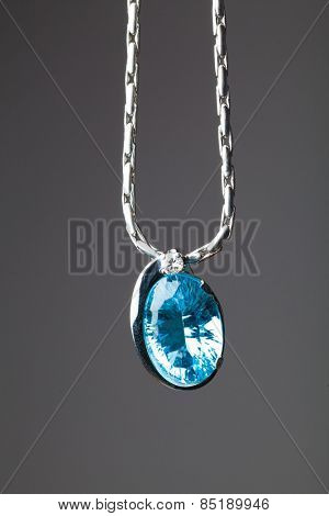blue sapphire pendant on grey background