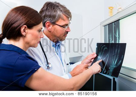 Doctor with x-ray picture of patient hand in his surgery examining the image
