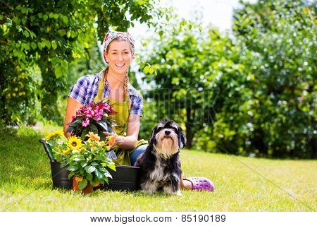 Woman in garden with flowers and pet dog