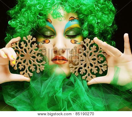 Beautiful lady with artistic make-up holding Christmas decorations.Doll style.