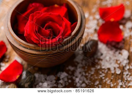 Roses in wooden bowl with pile of salt ,stones on old wooden board