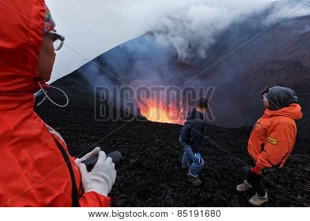 Eruption Tolbachik Volcano On Kamchatka, Travelers Watching The Lava Lake In Crater Of Volcano