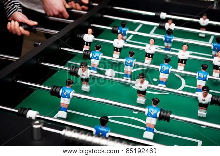 Friends having fun together playing table football.