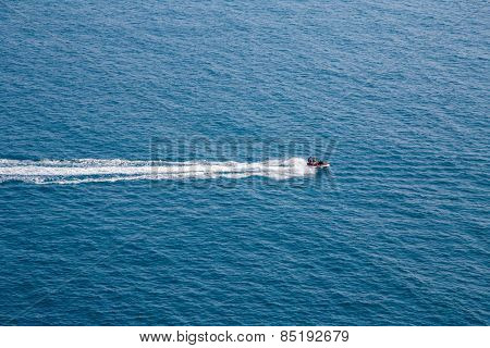 Aerial view on a couple driving a jet-ski at sea.