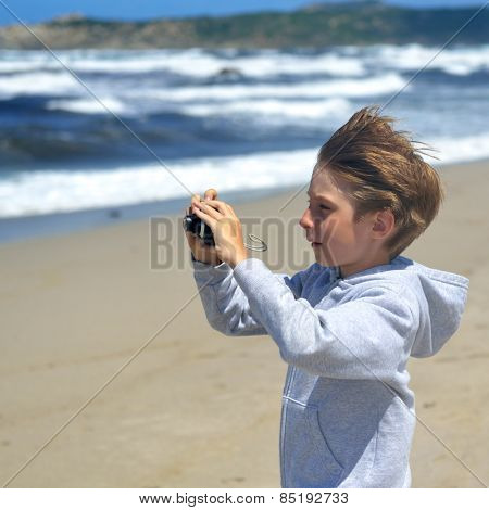 young boy makes photos with photo camera on the sea coast, toned