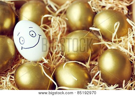 Egg with smiley face among golden eggs