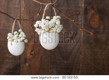 Bunch of of white baby's breath flowers (gypsophila) in eggs shell on the brown wooden plank. Shallow depth of field, focus on near flowers. Easter decor