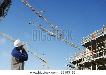 building worker directing large construction cranes