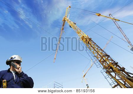 construction worker talking to crane driver inside building site
