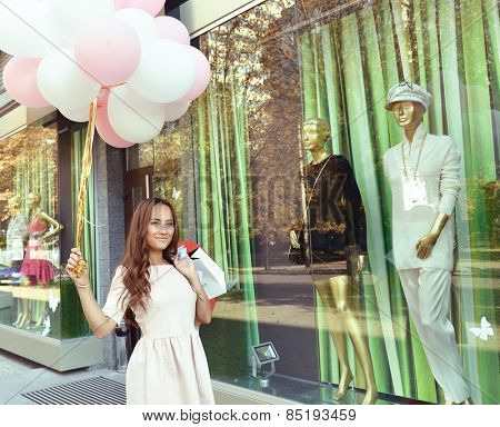 Beautiful young fashion woman holding shopping bags and standing near shop window, toned