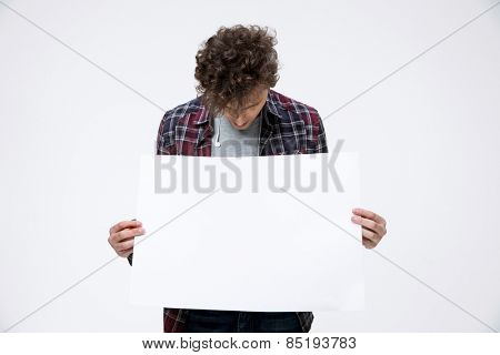 Young man holding blank billboard and looking on it