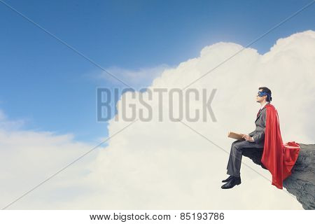 Young man in superhero costume reading book
