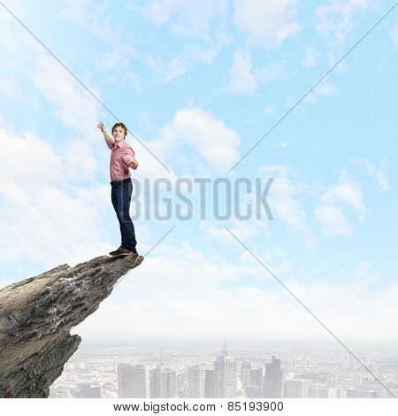 Young man balancing on one leg on edge of rock