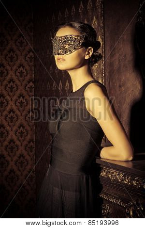 Beautiful mysterious stranger girl in venetian mask. Carnival, masquerade. Jewellery, gems.