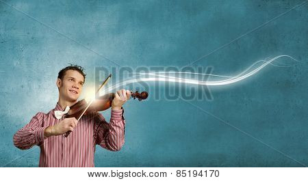 Young funny man in casual playing violin