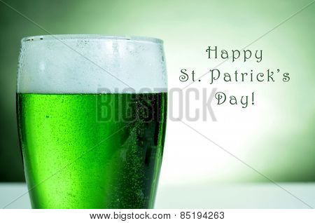 a glass with dyed green beer and the text happy saint patricks day