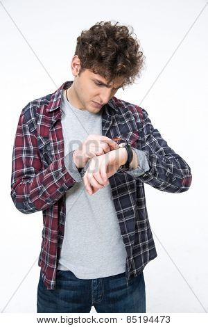 Casual man looking on the watch over gray background