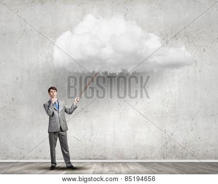 Young businessman pulling white cloud with rope