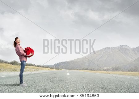Young girl with red santa bag in hands