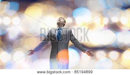 Joyful businessman with outstretched arms celebrating success