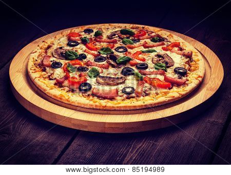 Vintage retro effect filtered hipster style image of ham pizza with capsicum, mushrooms, olives and basil leaves on wooden board on old table
