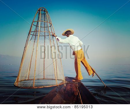 Vintage retro effect filtered hipster style image of Myanmar traditional Burmese fisherman with fishing net at Inle lake in Myanmar famous for their distinctive one legged rowing style, view from boat