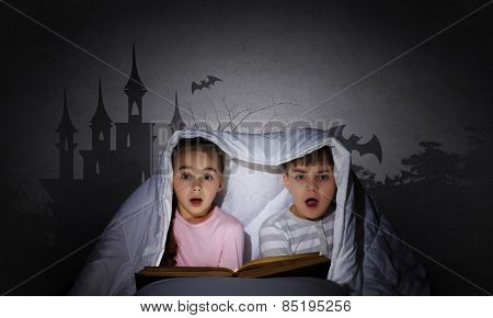 Children sitting in bed under blanket with book