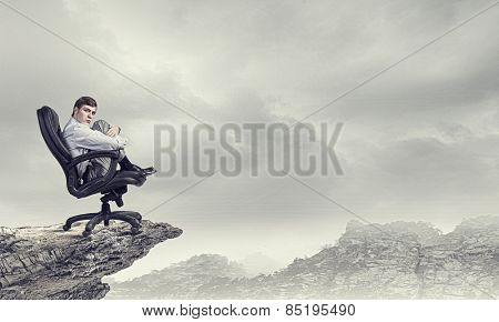 Frustrated young businessman sitting in chair in isolation