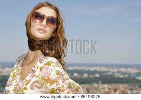 portrait of a beautiful attractive young adult sensuality and sexy pretty brunette woman in sunglasses on background blue sunlight sky