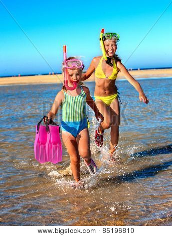 Two female children playing on beach.  Blue sky.