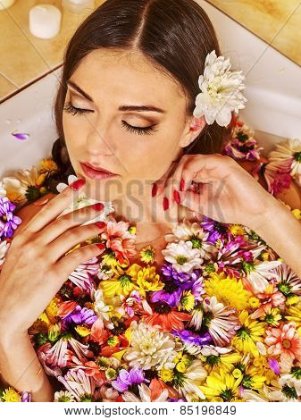 Woman applying moisturizer at bathroom.