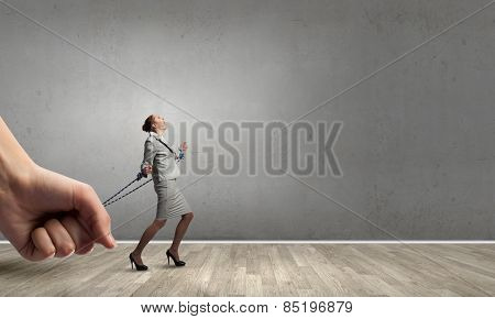 Young businesswoman with ropes on hands trying to escape