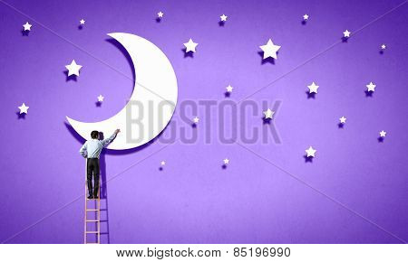 Rear view of man standing on ladder and reaching moon