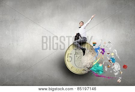Young businessman with briefcase riding euro symbol