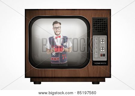 Geeky hipster offering christmas gift against retro tv
