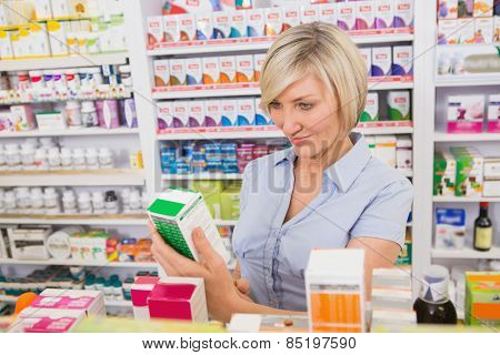 Smiling customer looking at medicine in the pharmacy