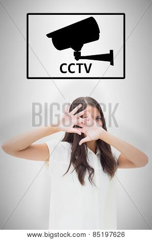 Fearful brunette covering her face against cctv