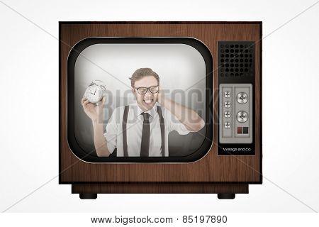 Geeky businessman holding alarm clock against retro tv